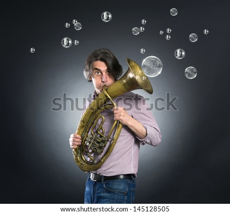 Adult man is playing on a big tube - stock photo