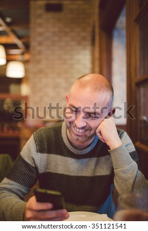 Adult man looking at his smartphone before eating in a restaurant - stock photo