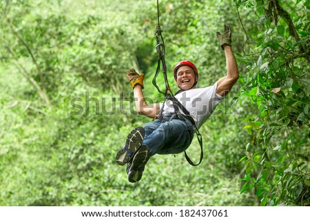 Adult man on zip line, Ecuadorian Andes - stock photo