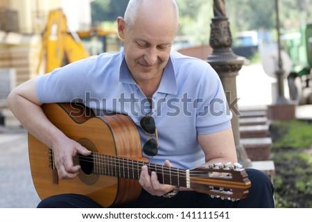 Adult man playing guitar outdoors. - stock photo