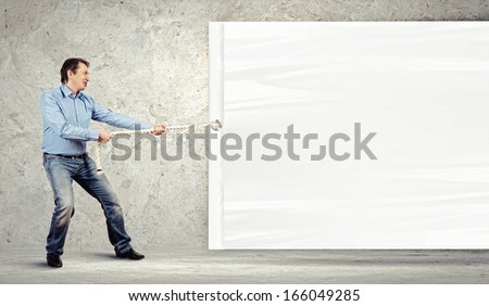 Adult man pulling blank banner. Place for text - stock photo