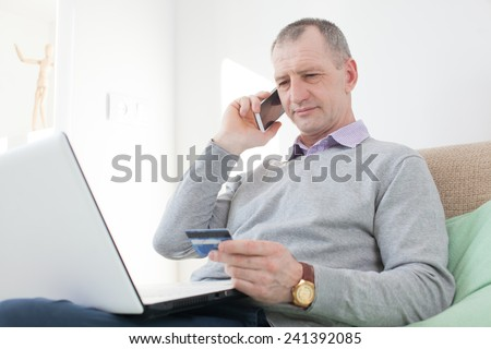 Adult man reading a credit card number during phone call - stock photo