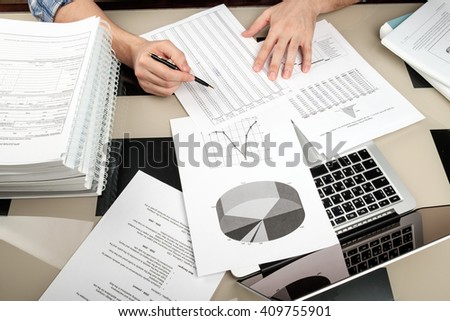 Adult man reading paperwork with graph and tables in home office with laptop