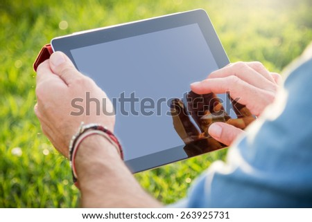 Adult man relaxing at the park with a digital tablet. Lens flare on the upper side of the image. Clipping path of the touch screen included.