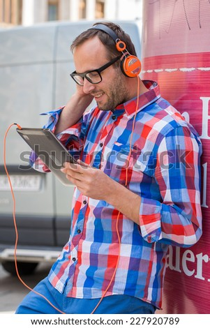 Adult man relaxing with headphones, listening to music. Orange fashionable headphones. He is dressed in shirts Checked. Outdoor - stock photo