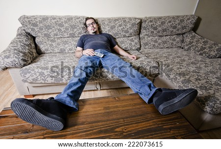 Adult man resting in sofa like a couch potato with remote control on belly - stock photo