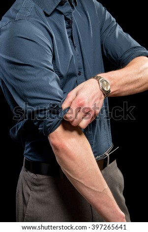 Adult man rolling up his sleeves. Studio shot over black. - stock photo