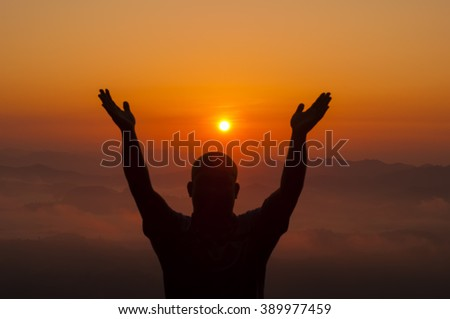 Adult man satisfied with nature beauty of sunrise. Photo from behind against the sun