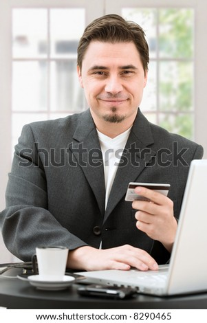 Adult man shopping online from home paying with credit card. - stock photo