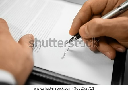 Adult man signing a document. The appeal is ready. Lawyer's work. Helping the organisation. - stock photo