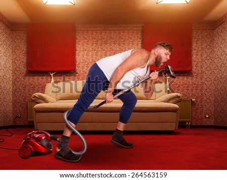 Adult man sings to the vacuum cleaner at home interior - stock photo