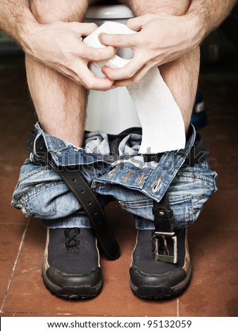Adult man sitting on bathroom or wc toilet bowl holding paper in hands and making poo - stock photo