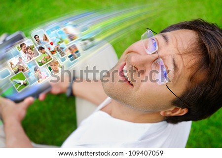 Adult man sitting on grass in park and using social media to look through new photo of his friends - stock photo