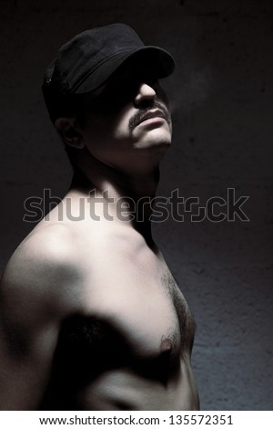 Adult man standing topless, smoke coming out of his mouth, on dark & blurry background of a brick wall. He is apparently looking at the camera, but his black cap completely shadows his eyes. - stock photo