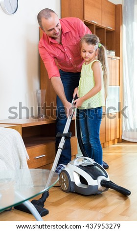 Adult man teaching little girl vacuuming during clean-up