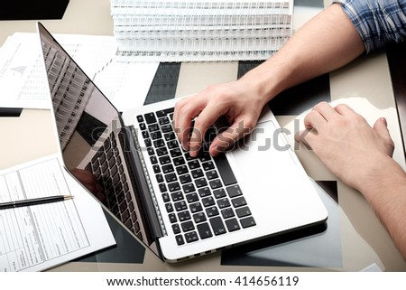 Adult man typing on laptop on glass table in home office