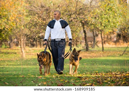 Adult Man Walking Outdoors With His Dogs German Shepherd - stock photo