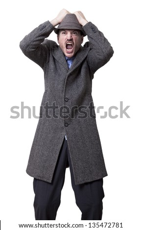 Adult man wearing a gray overcoat and hat. He's looking a bit upwards and screams in frustration while fiercely grabbing his hat with both hands. - stock photo