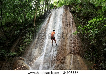 adult man wearing waterproof equipment descending a waterfall  - stock photo