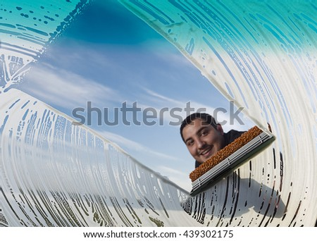 Adult man wiping windshield of his car. - stock photo