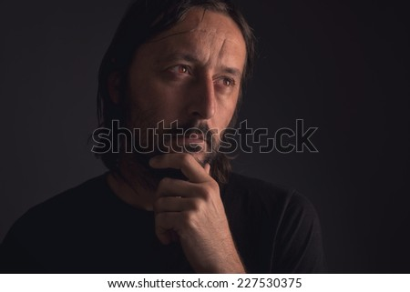 Adult man with beard thinking, low key portrait - stock photo