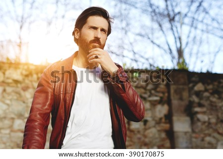 Adult man with serious face is looking away while standing outdoors in warm spring day during free time, bearded stylish hipster guy with fashionable look is waiting for someone in the fresh air  - stock photo