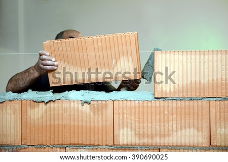 Adult mason while constructing a brick wall inside a house. Professional Bricklayer system a traditional orange brick above a line of industrial mortar. Close up of  worker dirty hand´s. - stock photo
