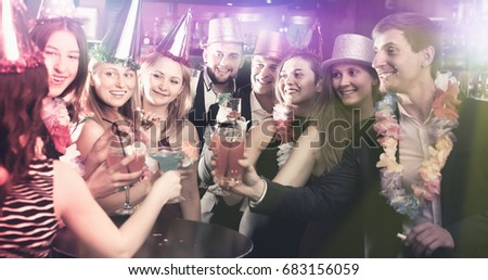 Adult men and women celebrating birthday in the bar at evening