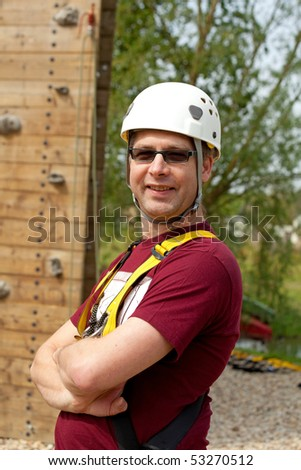 Adult men with helmet is posing before climbing wall - stock photo