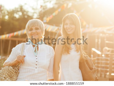 Adult mother and daughter after shopping walk down the street and talk - stock photo