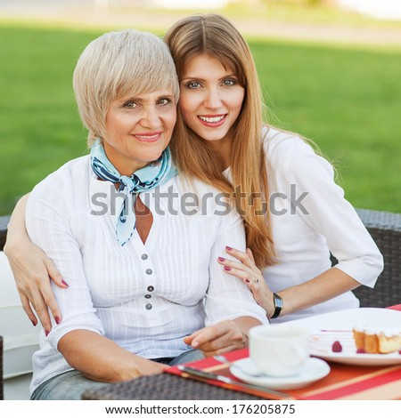 adult mother and daughter drinking tea or coffee and talking outdoors. Mothers day. - stock photo