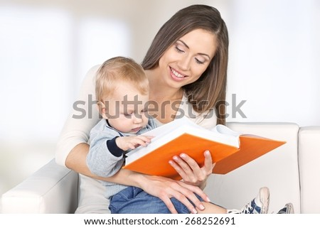 Adult. Mother reading a book a little baby daughter on the sofa at home - stock photo