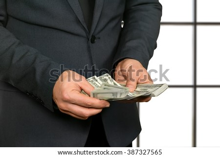 Adult office worker counting cash. Businessman in office counts salary. This should be enough. Such a pleasant view. - stock photo