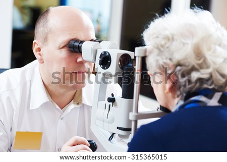Adult optometry. male optometrist optician doctor examines eyesight of woman patient in eye ophthalmological clinic  - stock photo
