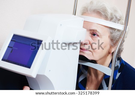 Adult optometry. Senior woman patient under eyesight examination in eye ophthalmological clinic  - stock photo