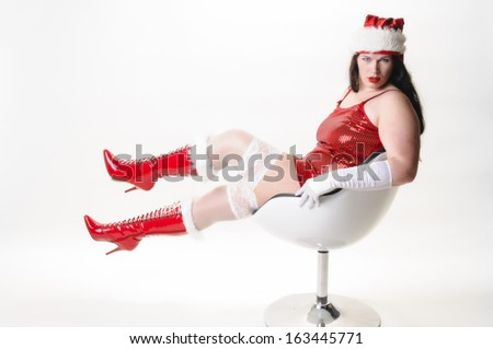 Adult overweight woman with long dark hair wearing a red Christmas coat and black boots. She sits on a chair and holding a golden Christmas gift in hand. You can see her red strapless socks.