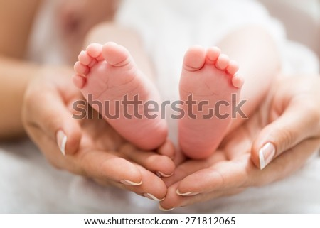 Adult. Parent holding newborn baby feet. family concept - stock photo