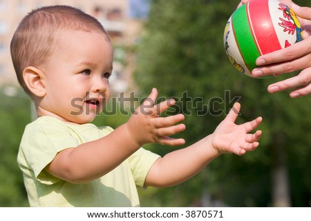 Adult pass ball to boy - stock photo
