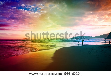 Adult people walking on a beach on sunny day. Young boys and girl enjoying a summer day in tropical paradise for travel, lifestyle business concept, blog, magazine. Image with rainbow color filter