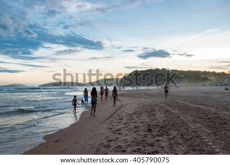 Adult people walking on the beach on sunny day  Young boys and girl enjoying a summer day in tropical paradise, image for travel, lifestyle business concept, blog, magazine - stock photo