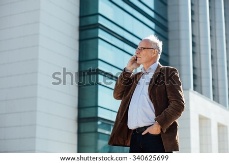 adult person with gray hair and eyeglasses, elegant dressed standing outside in front of an office building, speaking at cellphone - stock photo