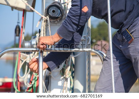 Adult sailor working on a yacht  in  natural environment with sun light