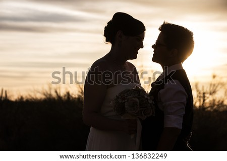 Adult same sex couple looking at each other at sunrise - stock photo