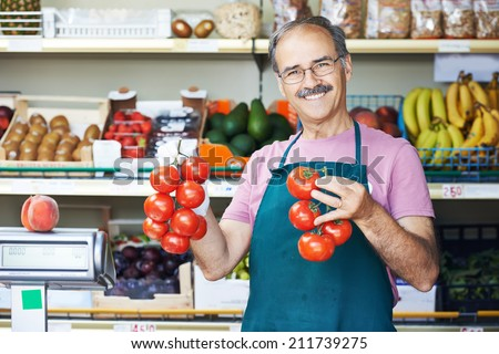 adult senior sale man with tomato at vegetable market shopping store - stock photo