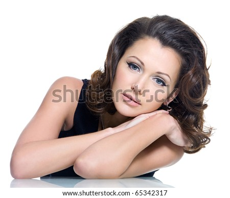 Adult sensuality beautiful brunette woman posing sitting from the white table over white background - stock photo