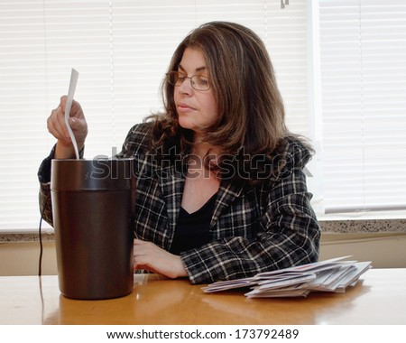 Adult shredding documents. Private information protection by a Latin business woman - stock photo