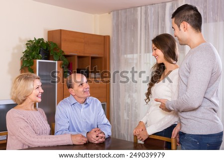 Adult smiling daughter introducing her boyfriend to parents indoor