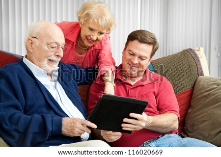 Adult son and elderly parents using their tablet PC at home. - stock photo
