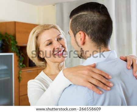 Adult son asking smiling mother to dance at home