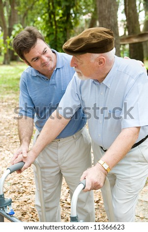 Adult son caring for his aging father who is confined to a walker. - stock photo